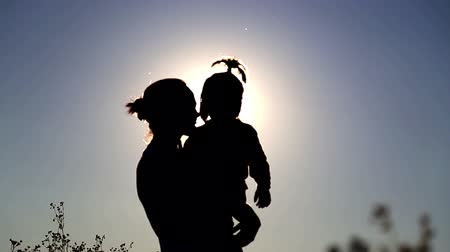 sunset light : Mum plays with children in the field.Mother and son blowing dandelion.Mother holding a baby in her arms.