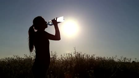 şişeler : Young woman drink water at sunset.Girl drinks water from a bottle (banks) Stok Video