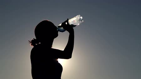 drink cans : Young woman drink water at sunset.Girl drinks water from a bottle (banks) Stock Footage
