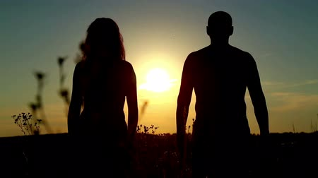 благодать :  Man and woman in a field at sunset.Couple in love at sunset.