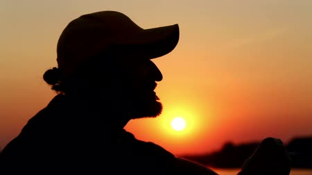 perfil : Portrait of a lonely man, smoking a cigarette at sunset.A man smokes a cigarette. Stock Footage