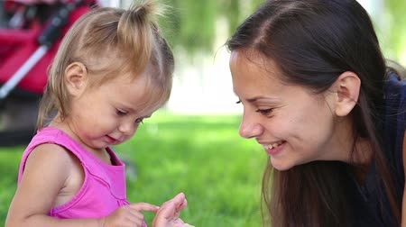 toy : Young mother with baby in a city park.Mother playing with baby in the park on the grass. Stock Footage