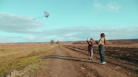 springtime : Caucasian boys flying a kite. Children playing in nature with a kite. Stock Footage