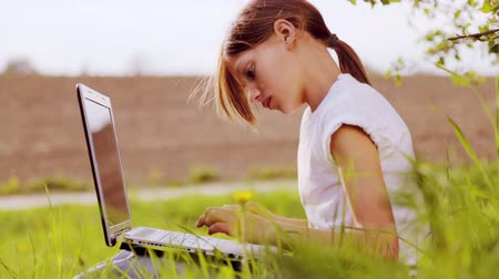 vila : Caucasian boy in the park with a laptop. A child with a laptop on nature. Country boy teenager with laptop. Vídeos