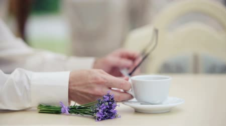 paylaşımı : Mans hand with a close up of a cup and a bouquet of lavender. Hand of man with glasses on the background of the book. Hand, book, cup, flower,