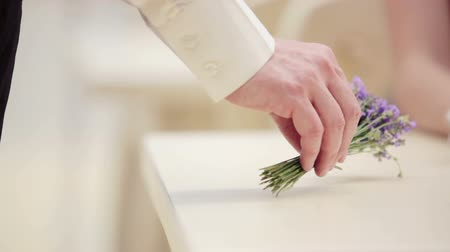 prst : Hand man closeup with a bouquet of lavender. Hands of men and women closeup with a bouquet of flowers. Mans hand lays down a bouquet of lavender on the table.