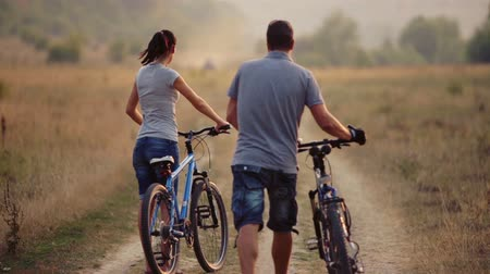 cyclists : A young couple enjoying cycling in nature. Man and woman walking, biking. Young enamored couple walking in a field. Sport, recreation, lifestyle. Stock Footage
