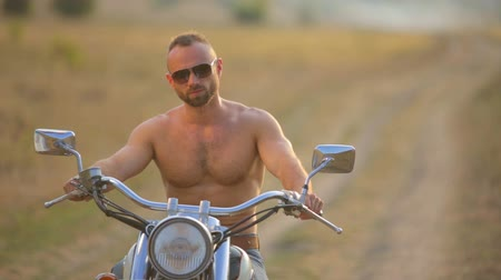 helmets : Young athletic man on a motorcycle. Portrait of a man on a motorcycle in the park. Stock Footage