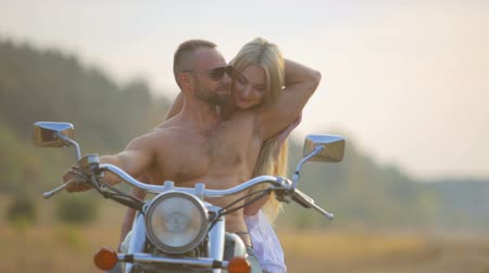 motocykl : Man and woman on a motorcycle outdoors. In love with a young beautiful couple on a motorcycle in the country. Sport, recreation, nature.