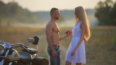 helmets : Man and woman on a motorcycle outdoors. In love with a young beautiful couple on a motorcycle in the country. Sport, recreation, nature.