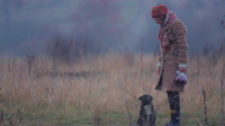 rescue dog : Young woman with a dog for a walk. Young girl with a dog in the field. Young woman in warm clothes in a field.