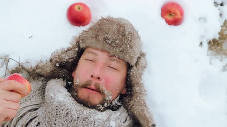 beardie : Portrait of a bearded man with an apple in the winter. A young bearded man eats an apple in the winter. The bearded man eating an apple to the camera in the winter.
