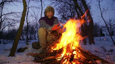 beardie : Bearded man warming his hands by the fire in winter. Tourist man evening campfire. A young bearded man at a fire in the woods. Stock Footage