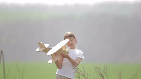 sen : Caucasian boy playing with a model airplane. Portrait of a child with a wooden plane in a field. Wideo