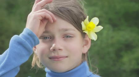 sen : Portrait of a boy in the spring with a flower of yellow narcissus. Conceited boy smelling flower narcissus. The boys face teenager with a flower in her hand. Wideo