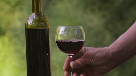 saborear : Red wine is poured into a glass. Composition with a bottle of wine and a glass. Winery, wine production.