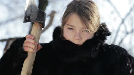 boyish : Portrait of a northern boy close up with an ax. Teen Boy in winter coat with a hatchet. Siberian boy with a stern face.