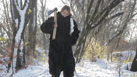 hangtompító : A teenager in a fur coat pulling firewood from the forest. Siberian boy with an ax in the forest. A boy in a fur coat in the winter in the village.