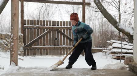 boyish : Boy removes snow shovel near the house. Cleaning snow in the winter near the house. The child cleans shovel the snow covered track.