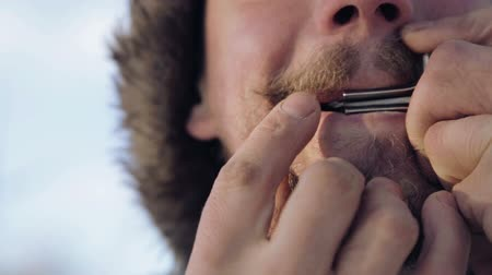 plucked : Portrait of a man playing a harp. The bearded shaman plays the harmonica drymba. Face closeup with a musician Jews Harp.