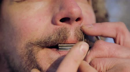 plucked : The bearded shaman plays the harmonica drymba. Face closeup with a musician Jews Harp. Face close up with a musical instrument Jews Harp (Sound file).