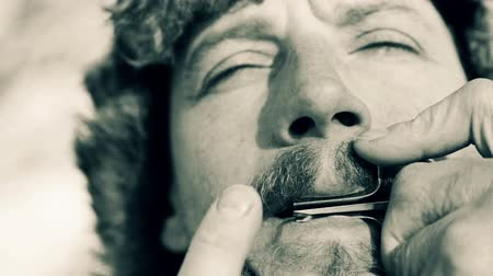 plucked : Portrait of a man playing a harp(black and white image). The bearded shaman plays the harmonica drymba(black and white image). Face close up with a musical instrument Jews Harp (Sound file)