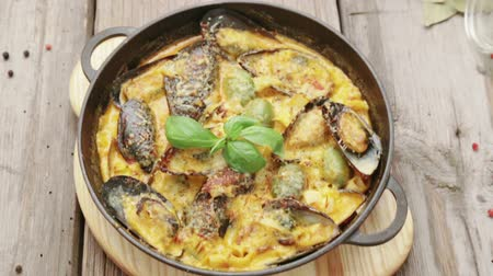měkkýš : Dish of mussels in a sauce on a wooden background with spices. Mussels with cheese.