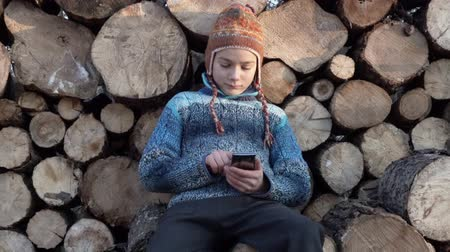 boyish : The boy is playing on the smartphone and hiding it behind his back. Portrait of a child on the background of a firewood playing on a smartphone. Stock Footage