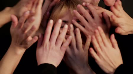 arcszín : The face of the girl close up is closed by a multitude of hands. Portrait of a womans face in a multitude of hands.