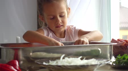 cheese making : Portrait of a little girl who helps her mother in the kitchen. Daughter helps mom in pizza making 4k video. The child learns to cook food.