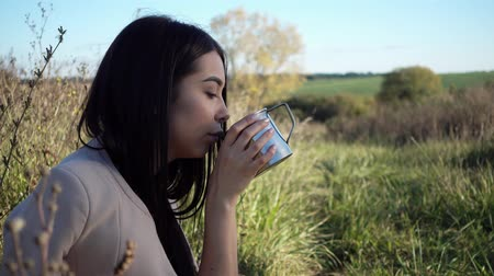 indian tea : Girl drinking tea in nature enjoying the beauty. Beautiful young woman resting with a mug of coffee in nature.