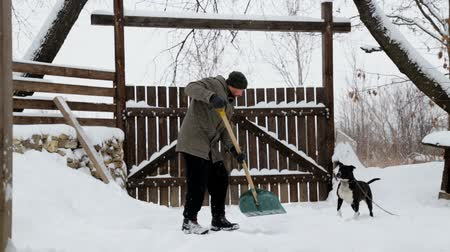 sokak : A young man cleans the snow in his yard. Bearded man cleans snow near his house.