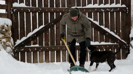 pikk : A young man cleans the snow in his yard. Bearded man cleans snow near his house.