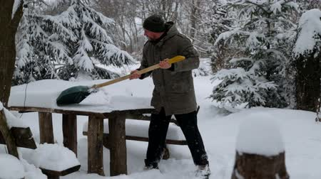 enredo : A young man cleans the snow in his yard. Bearded man cleans snow near his house.