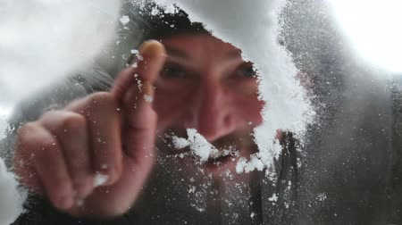 çizmek : A man wipes the snow A close-up portrait of a man who looks through a window.