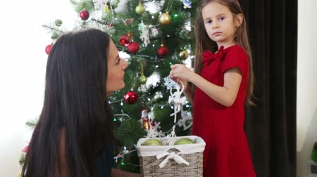 natale : Mother and daughter decorate the Christmas tree for the new year. A woman with a child girl decorates the Christmas tree.