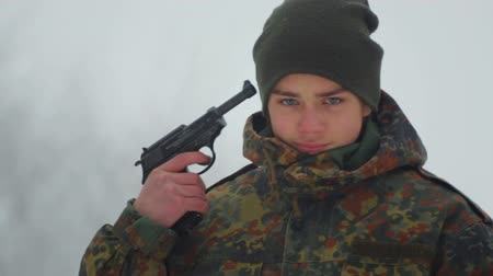 firearms : The boy is playing with a fake weapon. Portrait of a baby in camouflage clothes with a gun in his hands. Stock Footage