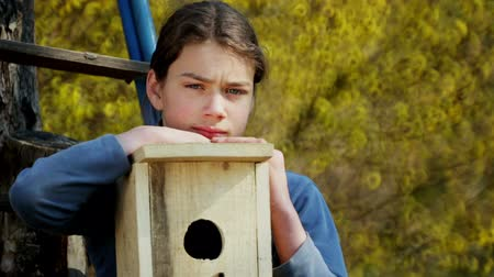 construct : Teen boy with a birdhouse for birds. A child makes and installs a birdhouse.