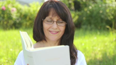 biblia : A young woman is reading a book in nature. A woman reads the bible in the park, relax, rest. Wideo
