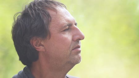 marijuana : Close-up portrait of a man with a cigarette in his hand. The face of a man with a cigarette in nature. Stock Footage