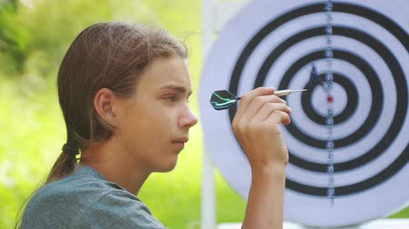 dart : Portrait of a teenager boy playing darts. A boy plays an outdoor darts game. Stock Footage