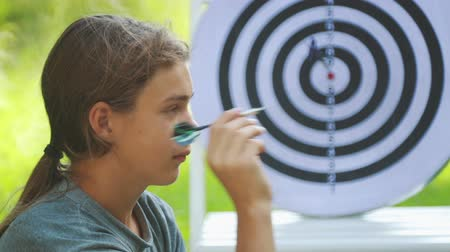 dartbord : Portrait of a teenager boy playing darts. A boy plays an outdoor darts game. Stockvideo