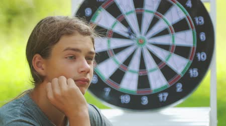 dart oyunu : Portrait of a teenager boy playing darts. A boy plays an outdoor darts game. Stok Video