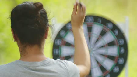 nape : Portrait of a girl from the back playing darts. Nape of a girl playing darts in nature. Stock Footage
