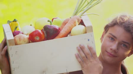 kitchen paper : A boy eats an apple and considers fresh vegetables. Teenage boy with a box of harvested fresh natural vegetables. Stock Footage