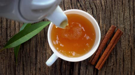 canela : Natural, hot, fresh tea with spices is poured into a mug, top view.