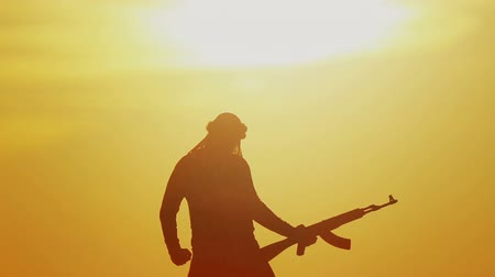 Islamic warrior with rifle at sunset day. Muslim fighter is training with a machine gun at sunset.