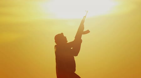 taktika : Islamic warrior with rifle at sunset day. Muslim fighter is training with a machine gun at sunset.