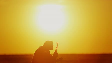 guerrilla : Islamic warrior with rifle at sunset day. Muslim fighter is training with a machine gun at sunset.