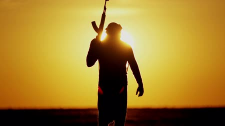 conflito : Islamic warrior with rifle at sunset day. Muslim fighter is training with a machine gun at sunset.